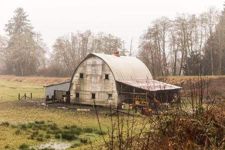 Weathered, old barn building in rainy Pacific Northwest landscape. Stock Photo