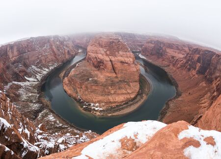 Horseshoe Bend in Paige, Arizona. Foggy winter day with snow on ground.
