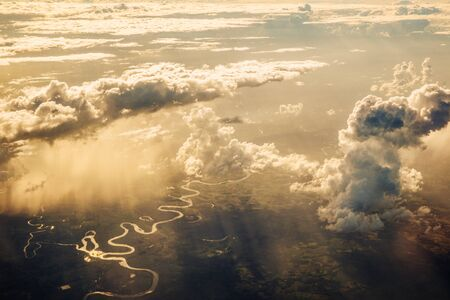 Aerial perspective of Guatemala (Central America). Winding river and green landscape visible under clouds.