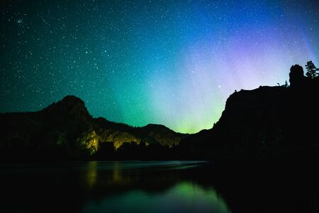 Northern lights or Aurora Borealis shining over mountains and reflecting on the Missouri River in Cascade, Montana, USA.