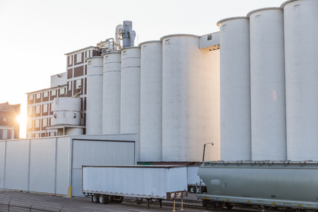 Large, white grain silos near shipping equipment and buildings at a mill.