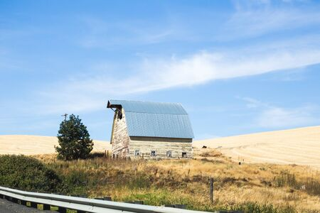 Vintage farm building under blue sky in the Palouse area of Washington state, USA. Stock Photo