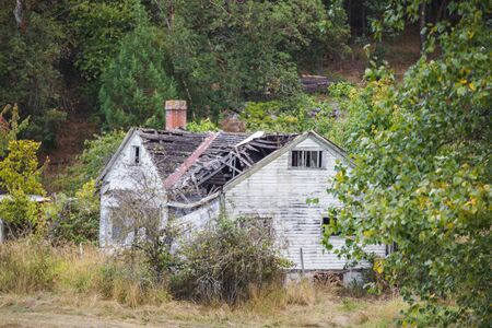 Old neglected house with roof caving in. Lush forested setting. Stock Photo