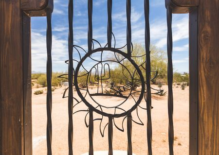Metal cactus and sun shapes in an outdoor gate in a desert area. Stock Photo