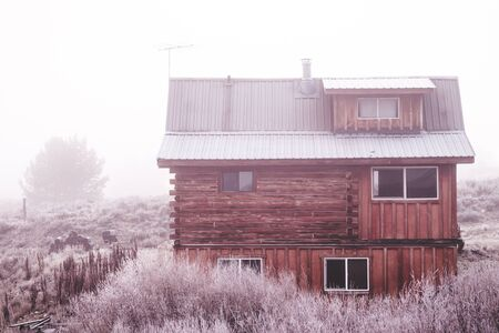 Small log cabin in frigid winter landscape (Stanley, Idaho, USA). Stock Photo