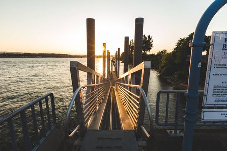 Sun setting over a metal ramp on the shore of the Columbia River in Vancouver, Washington, USA. Stock Photo