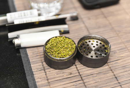 Ground cannabis inside a steel grinder thats been opened and set on a table placemat. Lighter and other marijuana-related items can be seen in background.