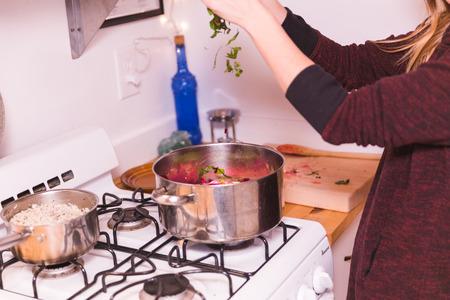 La mujer arroja verduras de hoja verde en una olla mientras prepara la cena. Ajuste de la cocina casera con estufa de gas. Foto de archivo