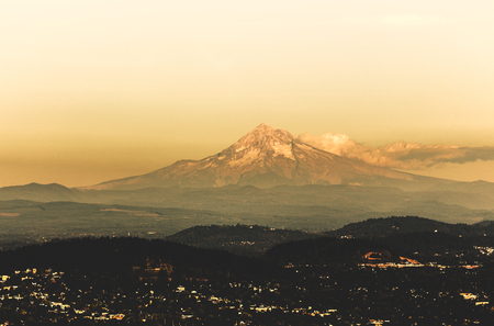 Clouds float against Mount Hood on a hazy day in Portland, Oregon, USA. Mount Hood is a potentially active volcano, one of many in the Pacific Northwest. Banco de Imagens