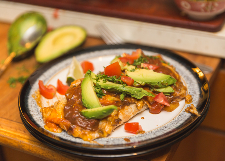 Burrito or enchilada on plate in kitchen setting. Ingredients include tortilla, cheese, peppers, avocados, tomatoes, and lime.