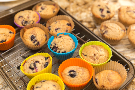 Homemade blueberry muffins baked in colorful silicone cups, cooling on a baking rack in a kitchen. Banco de Imagens