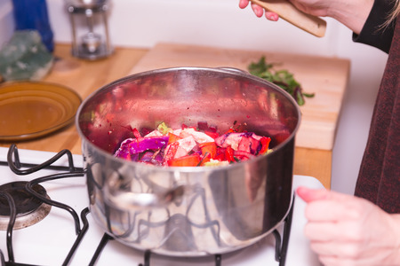 Pot cooking on gas stovetop burner with variety of colorful vegetables like peppers, tomatoes, and onions.