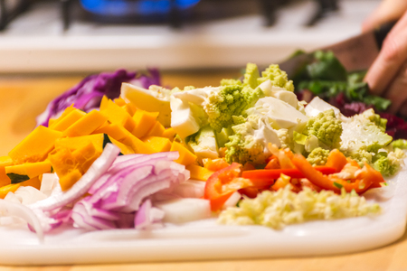 Piles of chopped vegetables on a wooden cutting board or chopping block. Vegetables include squash, onions, peppers, and romanesco broccoli.