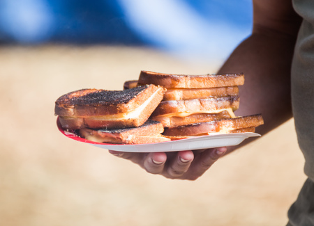 Stacks of grilled cheese sandwiches on a paper plate. Overweight man holding plate. Sandwiches are burnt and contain processed cheese and white bread. Banco de Imagens