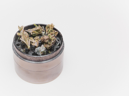Steel grinder with green cannabis flower (buds) inside.