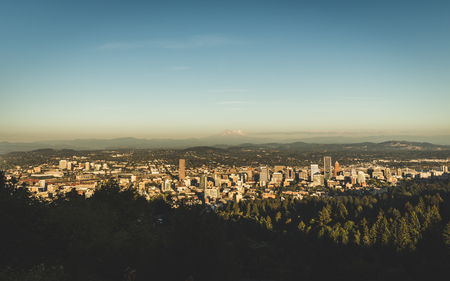 A gray haze rests over the city as the sun sets in Portland, Oregon, USA.