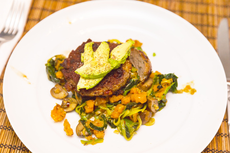 Homemade meal on white ceramic plate and textured table. Meal contains meat or meat substitute, leafy greens, mushrooms, sweet potatoes, avocado, and spices like cayenne pepper and salt.