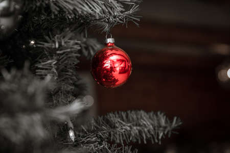 Red, round Christmas tree ornament shines against black & white background.