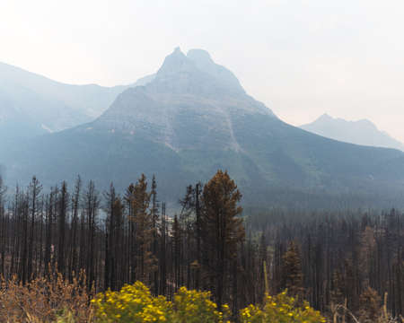 Smoky or hazy mountains in Glacier National Park, Montana. Forest fire smoke fills Glacier National Park on a late summer or fall day.