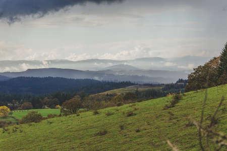 Rolling green hills and grassland with clouds and rain overhead. Farmland landscape captured in rural northwest Oregon, USA. Zdjęcie Seryjne