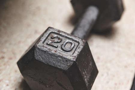 Twenty-pound dumbbell on floor. Gray dumbbell with engraved