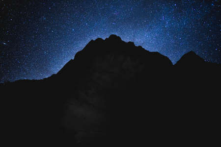 Stars shine above a silhouette of a mountain in Zion National Park, Utah, USA. Black mountain silhouette against bright night sky on a clear winter night. Zdjęcie Seryjne