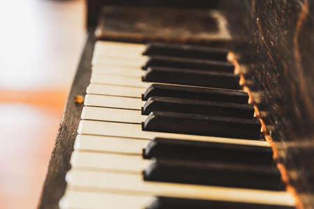 Close up details of keys on a vintage or antique piano. Wooden upright piano keys. Keyboard of old piano.