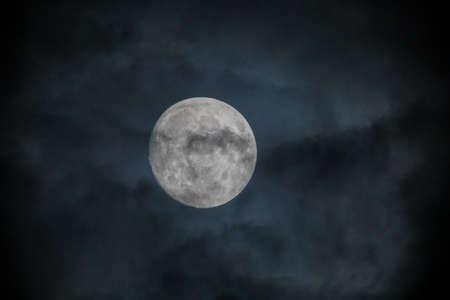 Full moon captured behind clouds in night sky. Dark clouds cover a bright white full moon. Captured in Summer 2020 near Portland, Oregon. Zdjęcie Seryjne