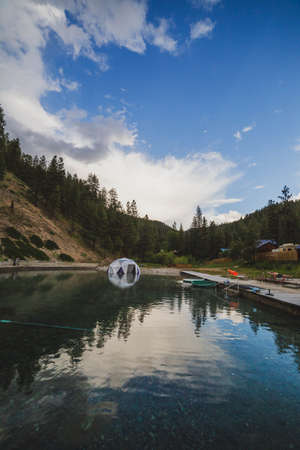 Blue sky with clouds over a pristine and reflective hot spring pool in the mountains. Captured in Idaho, USA.