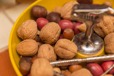 Hard-shell nuts like walnuts and pecans inside a yellow bowl, with metal nutcracker and digging tool. Zdjęcie Seryjne
