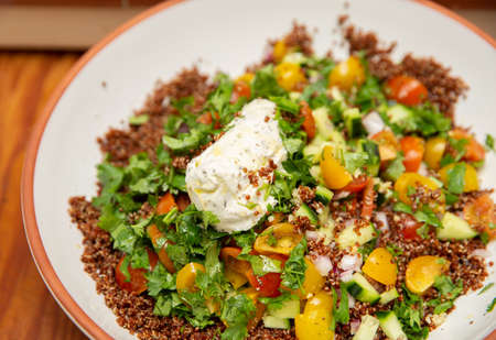 Quinoa salad with yellow bell peppers, cherry tomatoes, cucumbers, and cilantro or parsley. 版權商用圖片