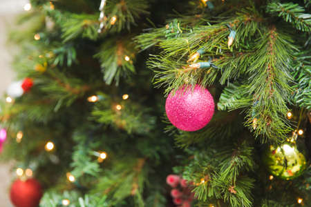 Shimmering and sparkling glass ornaments hang in a green Christmas tree. Traditional Christmas ornaments in tree.