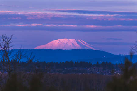 Purple and pink sunset lights up a snowcapped Mount St. Helens in Washington, USA. Captured from north Portland, Oregon, USA.