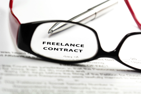 Freelance contract through reading glasses. 스톡 콘텐츠 - 114746388