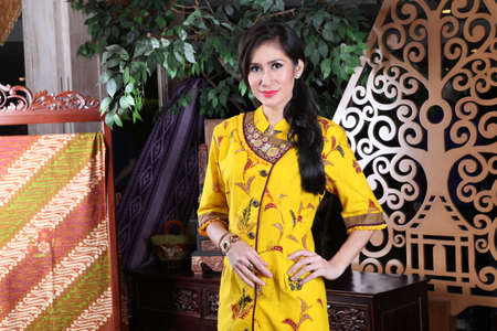 Beautiful woman wearing an elegant batik dress, Batik is a fabric that is painted using canting and liquid wax night so as to form paintings of high artistic value from Indonesia
