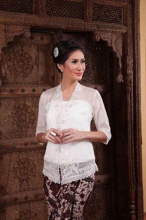Beautiful woman wearing an elegant kebaya, kebaya is a traditional dress worn by Indonesian and Malaysian women made from gauze cloth worn with batik.