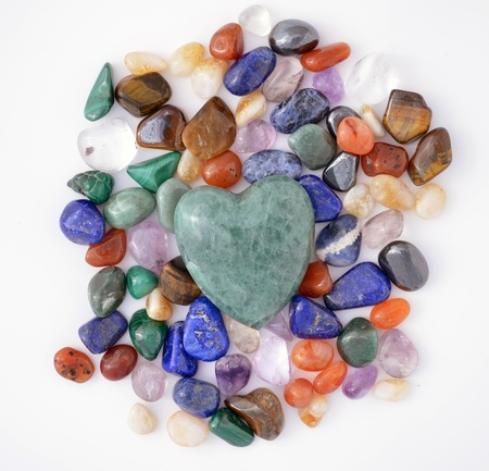 crystals: Green quartz heart on multicoloured pebbles of semiprecious stones