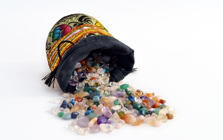 semiprecious: Quartz and other semiprecious pebbles pouring out of a decorated sacket