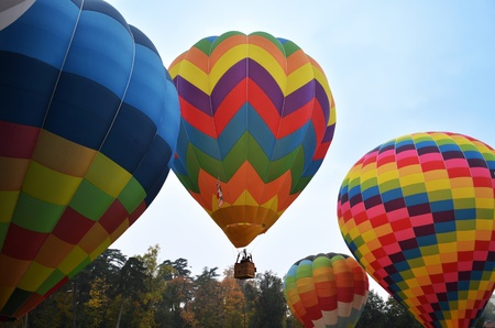 One hot air ballon taking flight over 3 other hot air balloons on the ground in a sunny day Stock Photo