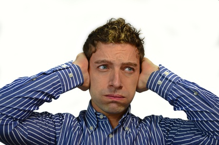 covering: Too much noise: attractive young man covering his ears Stock Photo