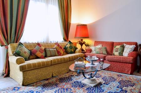 깔개: 고전 찾고 소파, 화려한 커튼, 램프, 유리 테이블과 우아한 거실 스톡 사진