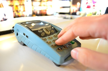 Closeup of hand typing payment details on POS machine in a store photo