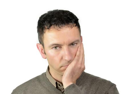 homme triste: Bon homme youg regardant avec la main sur son visage en raison de maux de dents Banque d'images