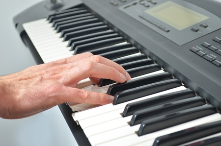 Single hand on electronic synthesizer playing music photo
