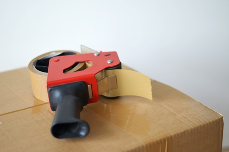 Self-adhesive tape dispenser on brown cardboard box photo
