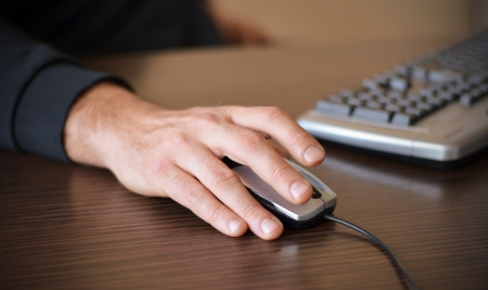 detail internet computer: Hand of a man working at computer clicking on mouse on dark desktop Stock Photo