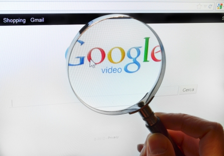 internet search: Magnifing glass over Google Video page Editorial