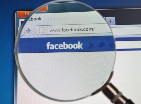 Search Facebook website with magnifying glass
