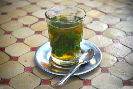 Glass of traditional mint tea and metal spoon and saucer photo