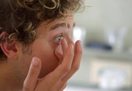 lentes de contacto: Chico guapo aplicación de lentes de contacto, vista lateral Foto de archivo